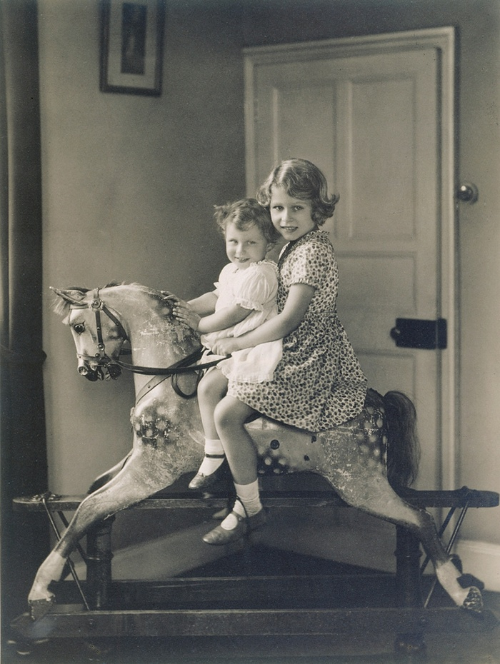 Princess Elizabeth and Princess Margaret riding a rocking horse in 1932